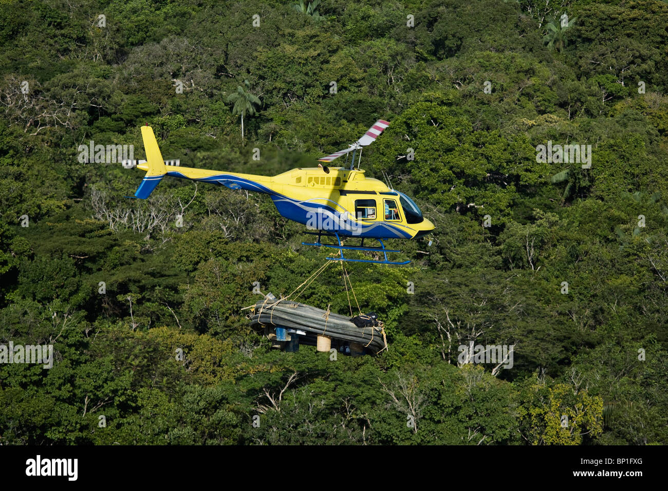 Helicopter transporting mining equipment for miners working in the Venezuela forest - Stock Image