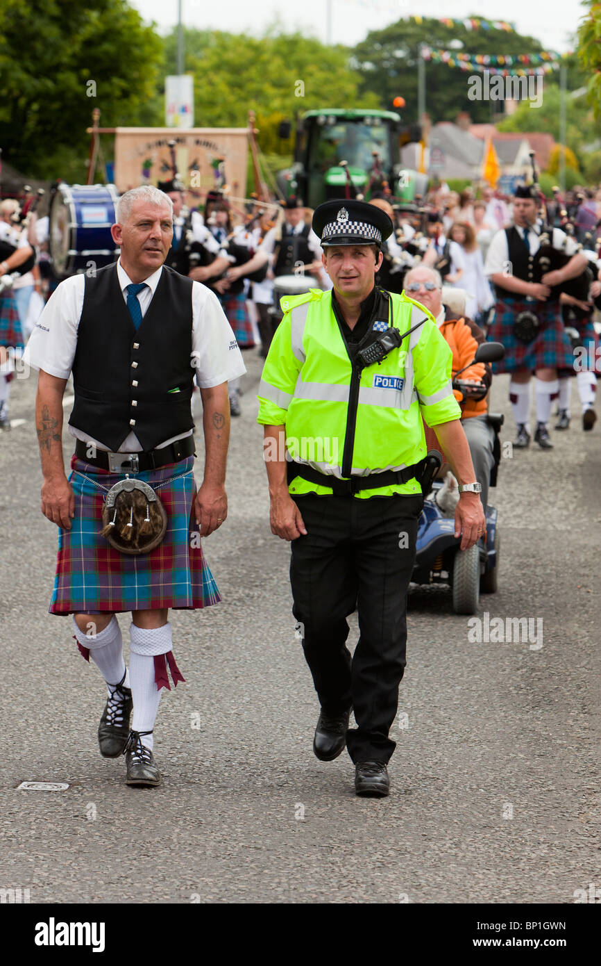 Pipe band member and policeman marching - Stock Image