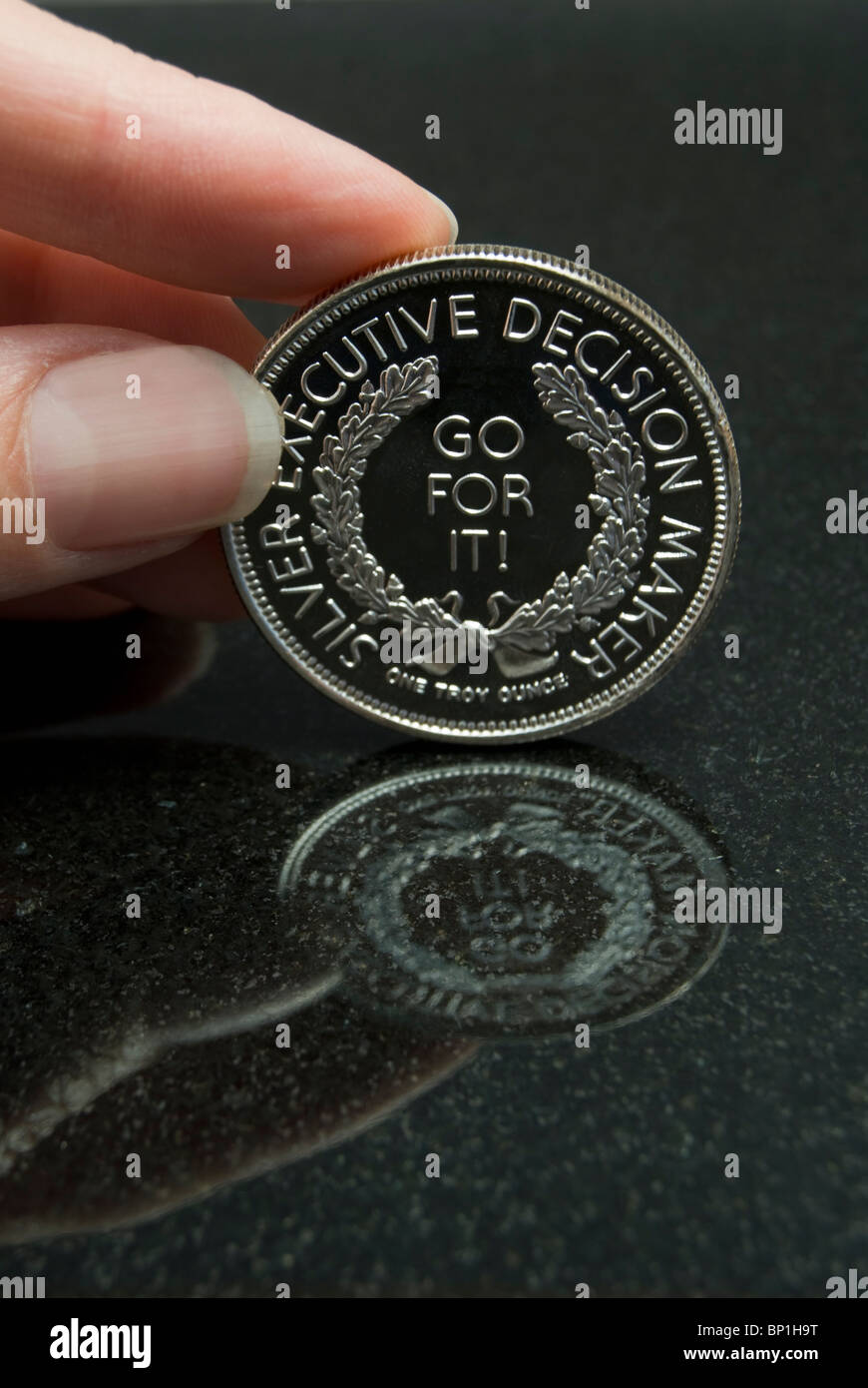 Female hand holding Executive Decision Maker silver coin