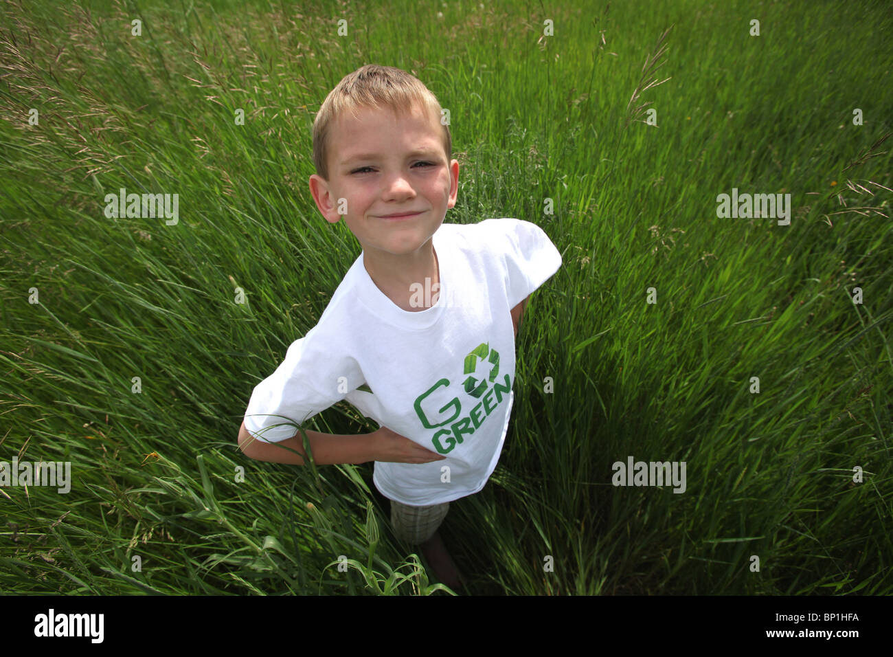 boy standing in tall green grass wearing 'go green' tee shirt - Stock Image