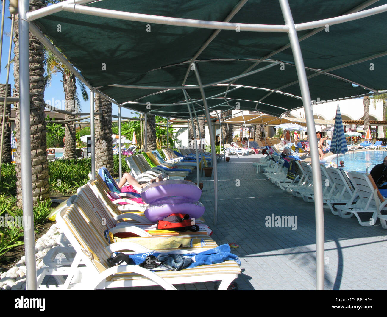 Sun loungers in the shade, with towels on reserving them - Stock Image