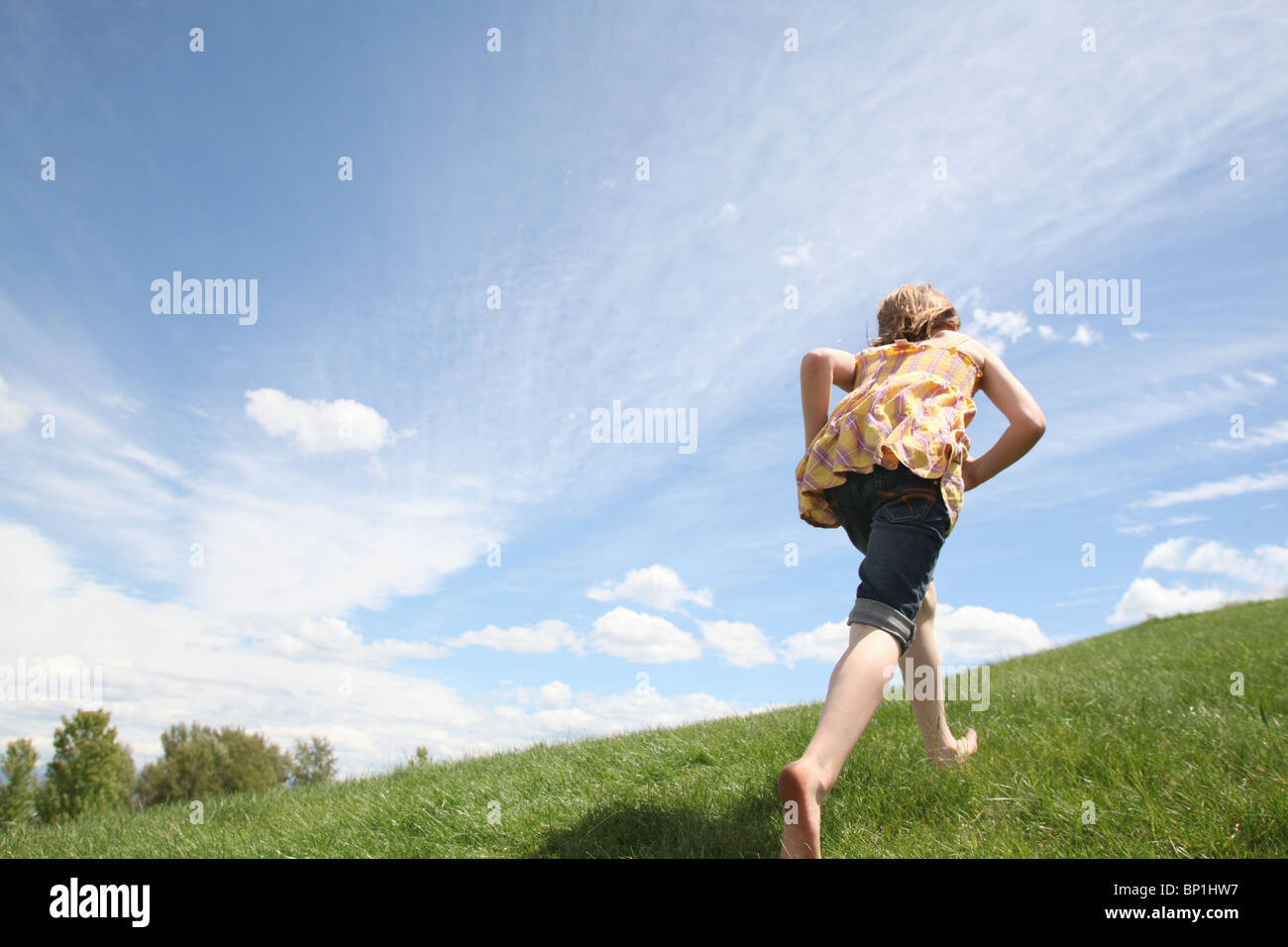 young girl running up green grass hill - Stock Image