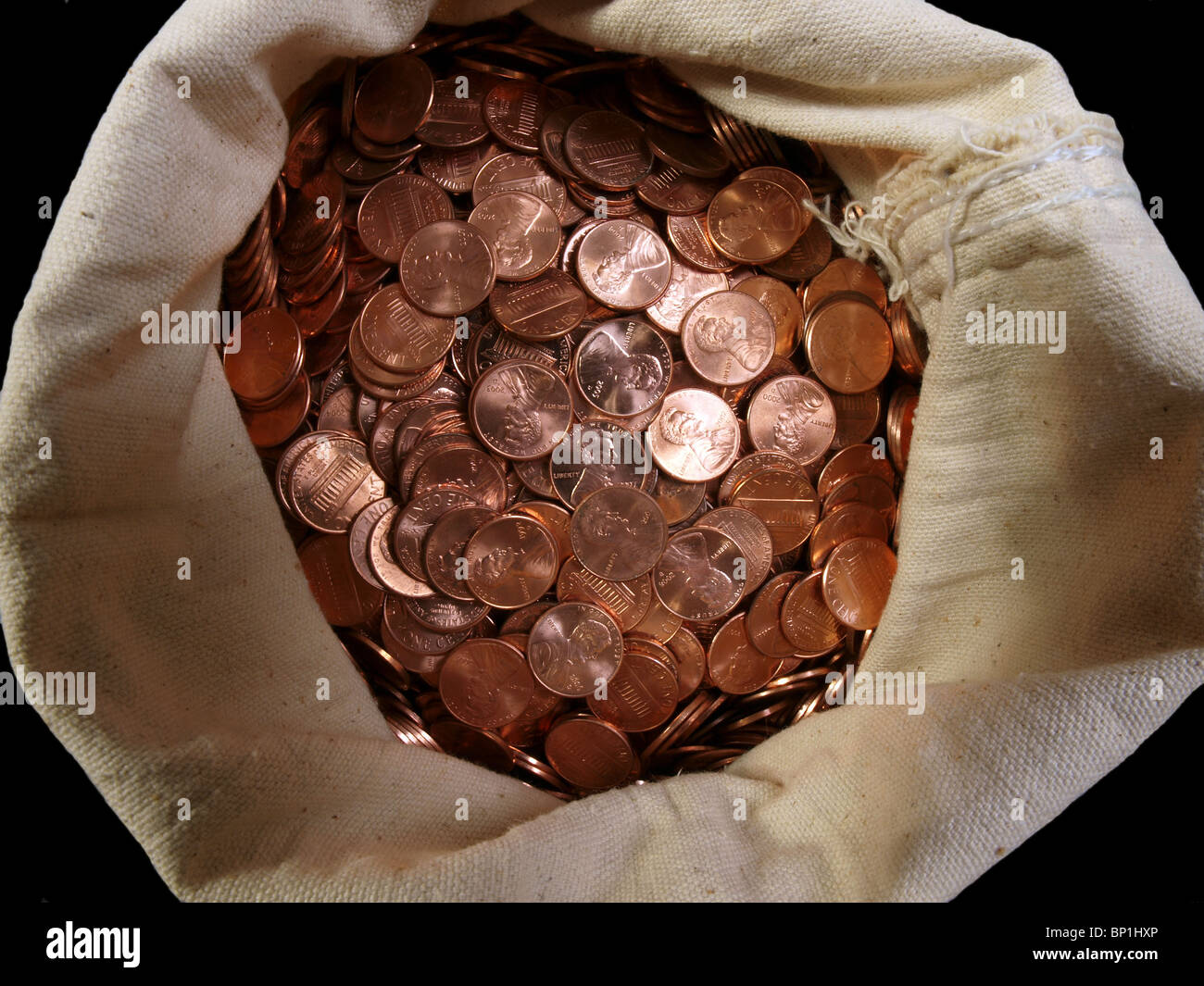 Shiny, new pennies in a vintage canvas money sack. - Stock Image