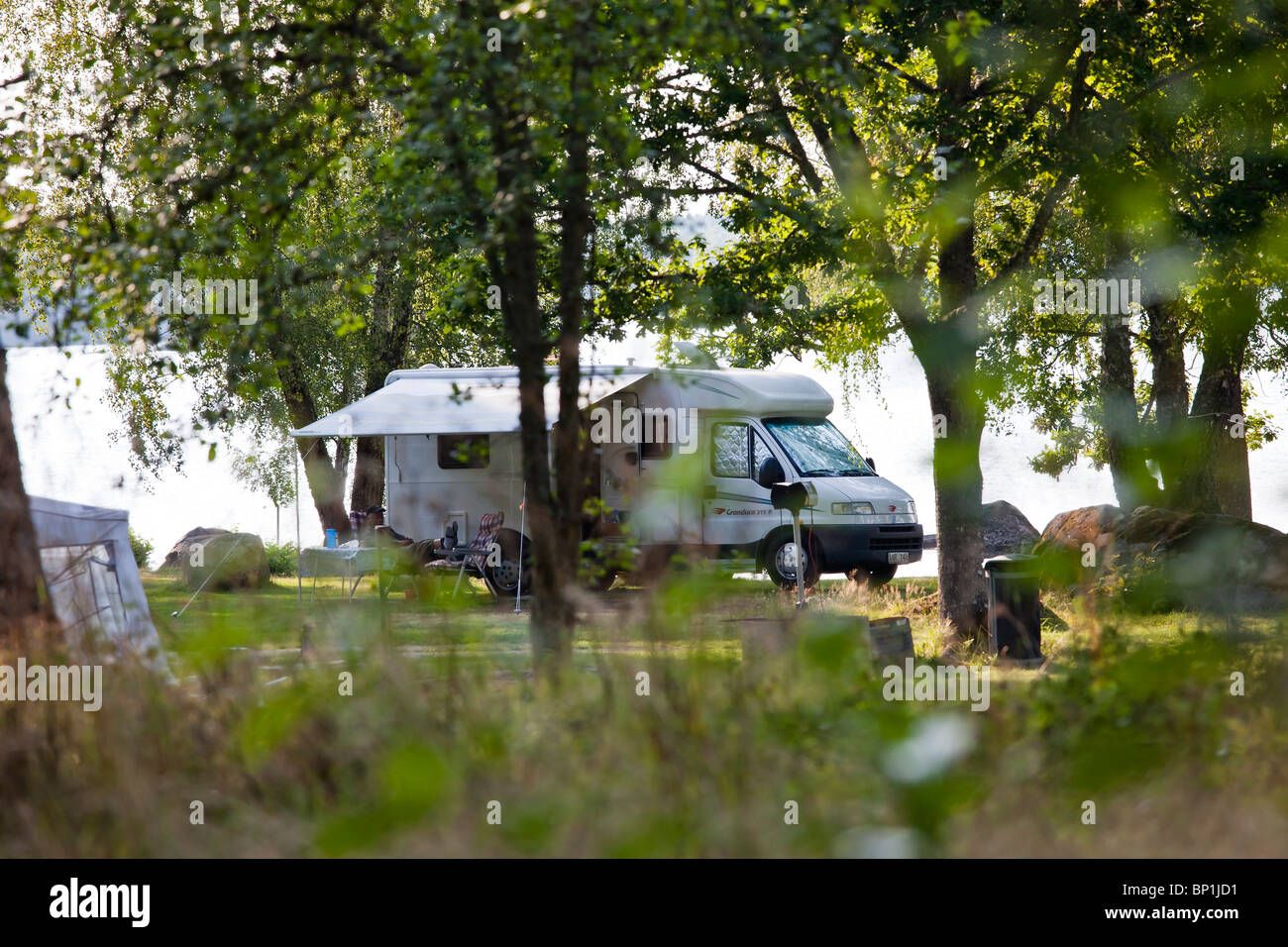 A camper parked at a lake, a man is sitting in the shadows relaxing - Stock Image
