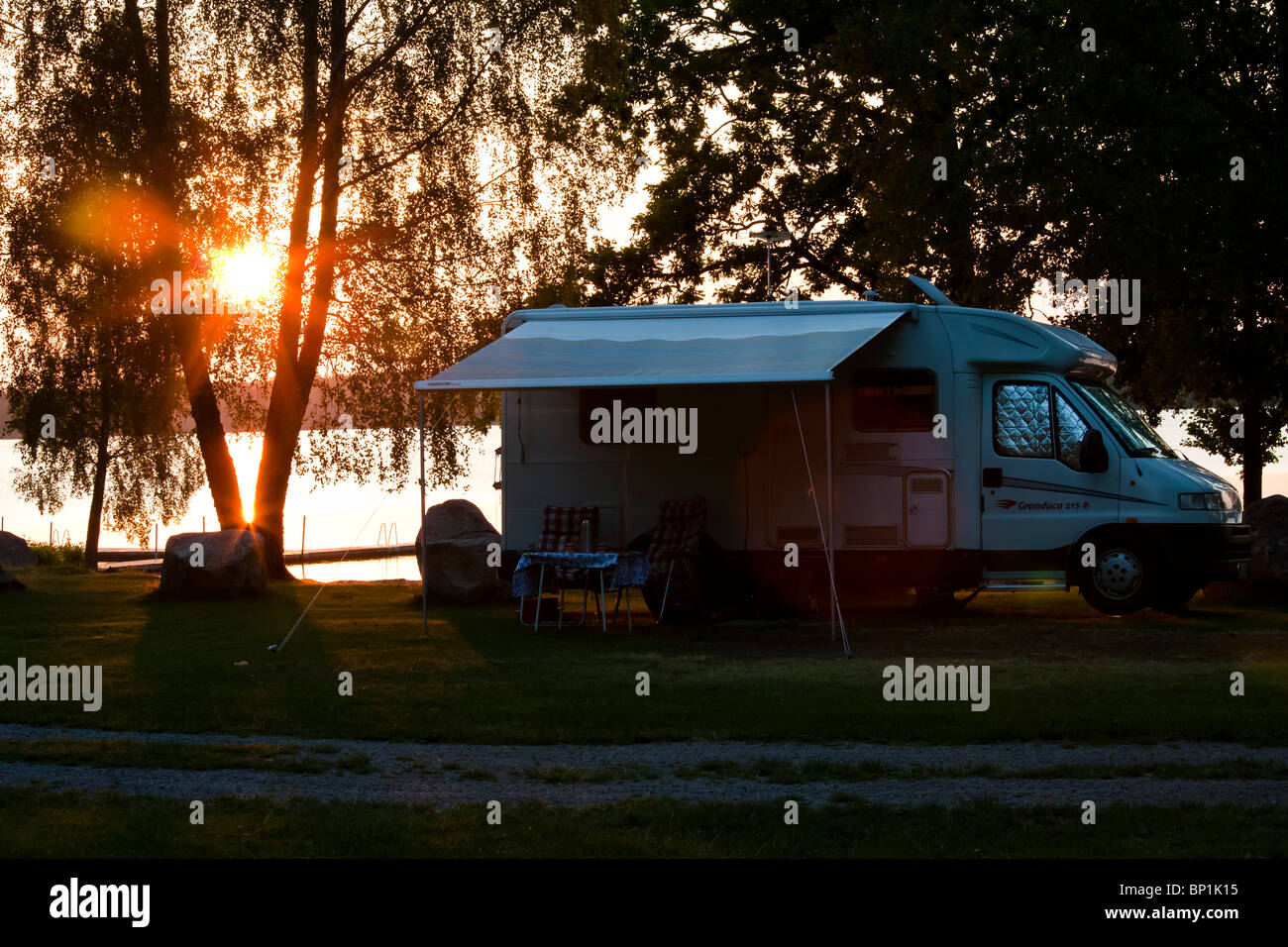 A camper trailer at a lake in sunset. - Stock Image
