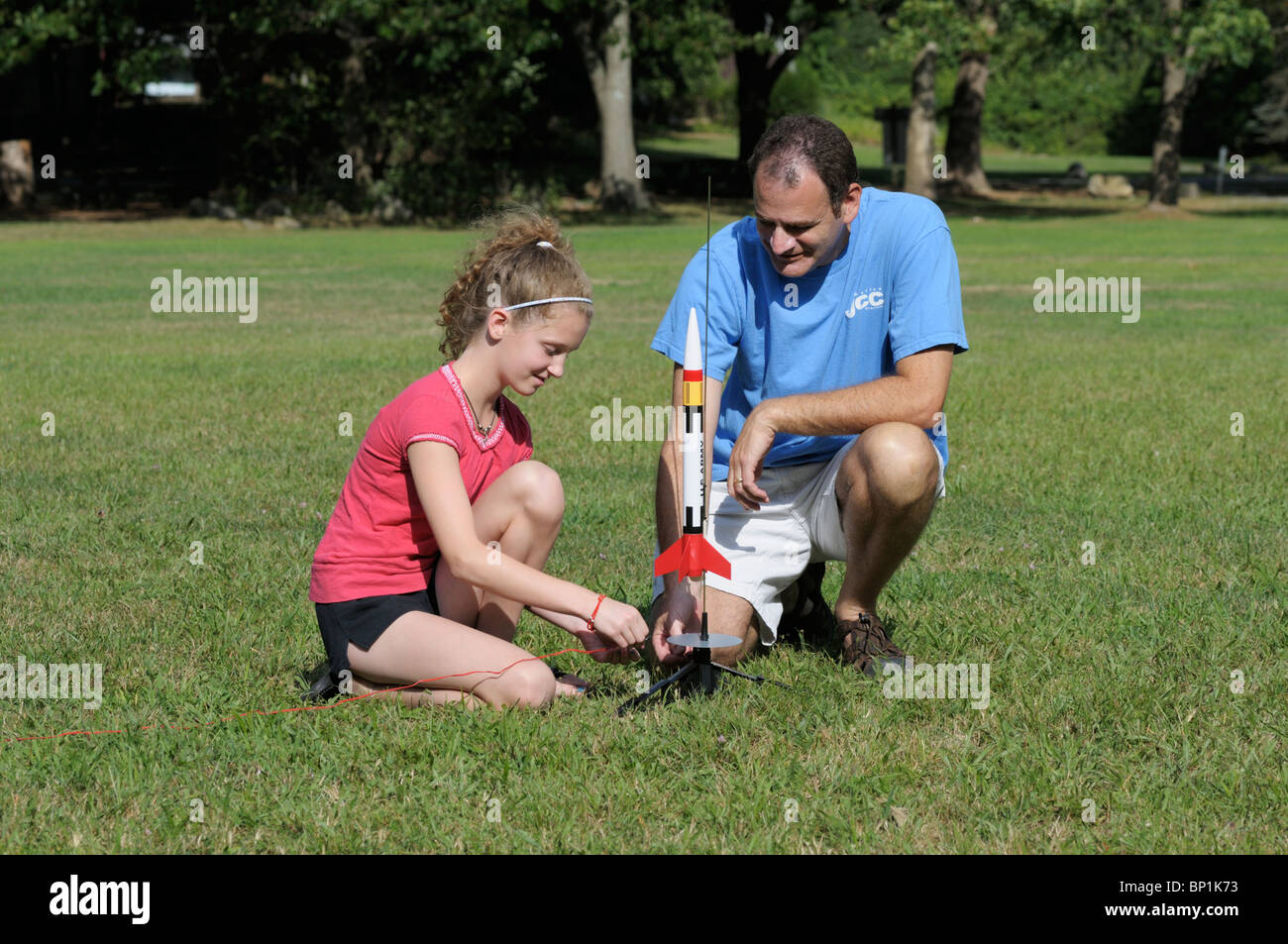 Girl, 11-12, and her father setting up a model rocket to launch. - Stock Image