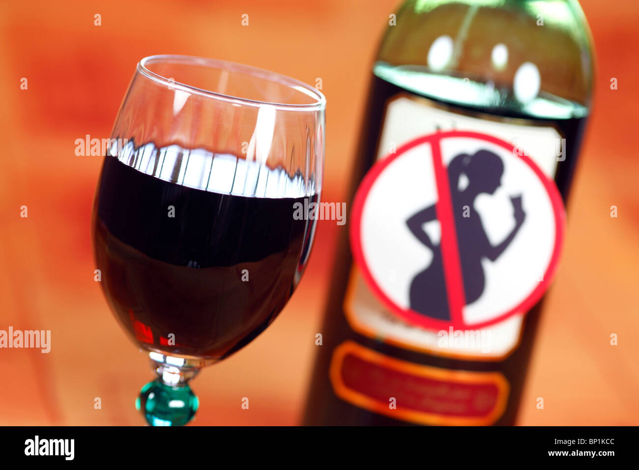 Glass and bottle of red wine with 'Unsuitable for pregnant women' sign - Stock Image