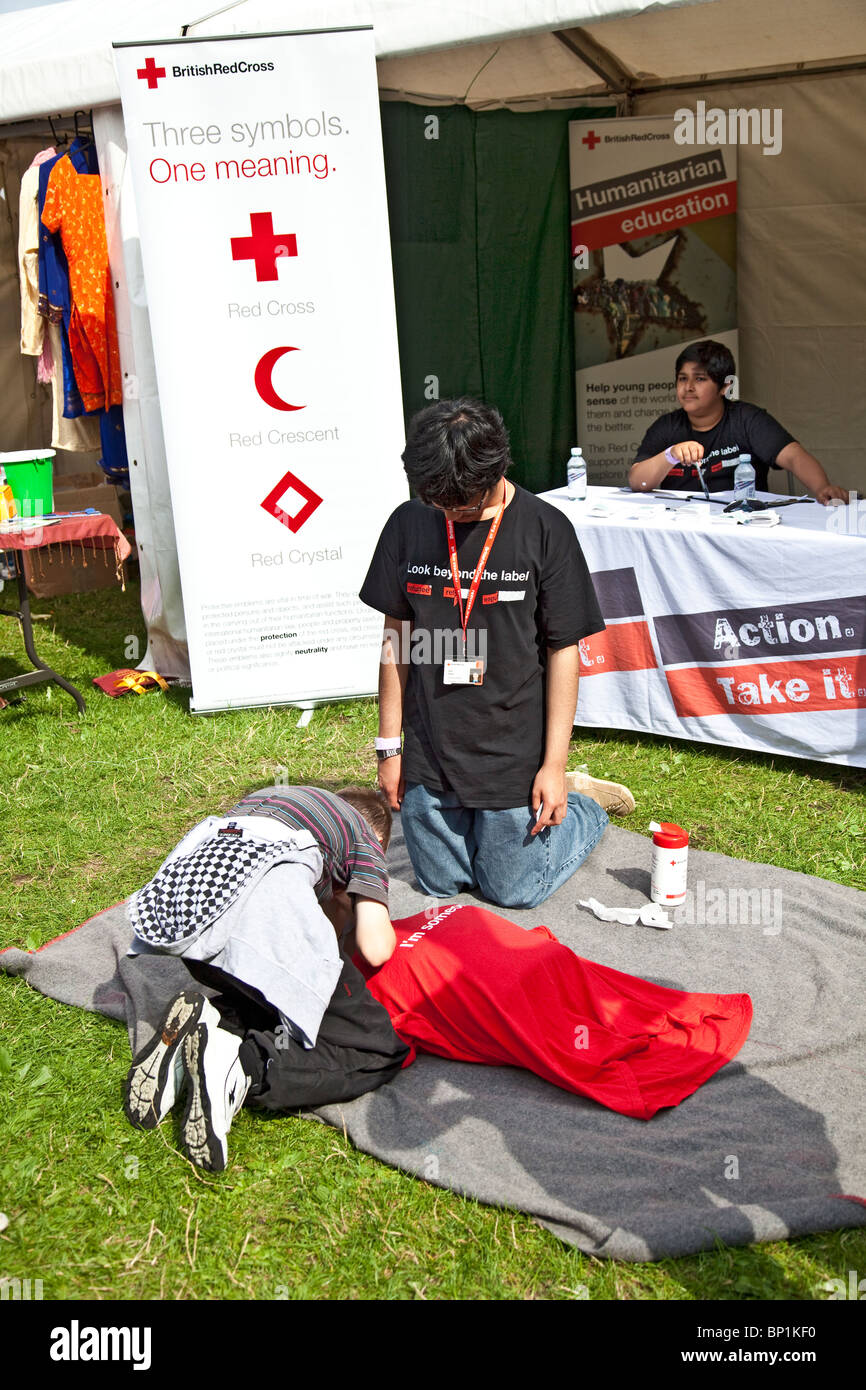 Young volunteer at the British Red Cross stand at Edinburgh Mela 2010 instructing a boy in artificial respiration - Stock Image