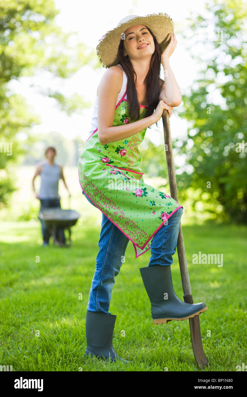 Young woman with foot on a spade - Stock Image