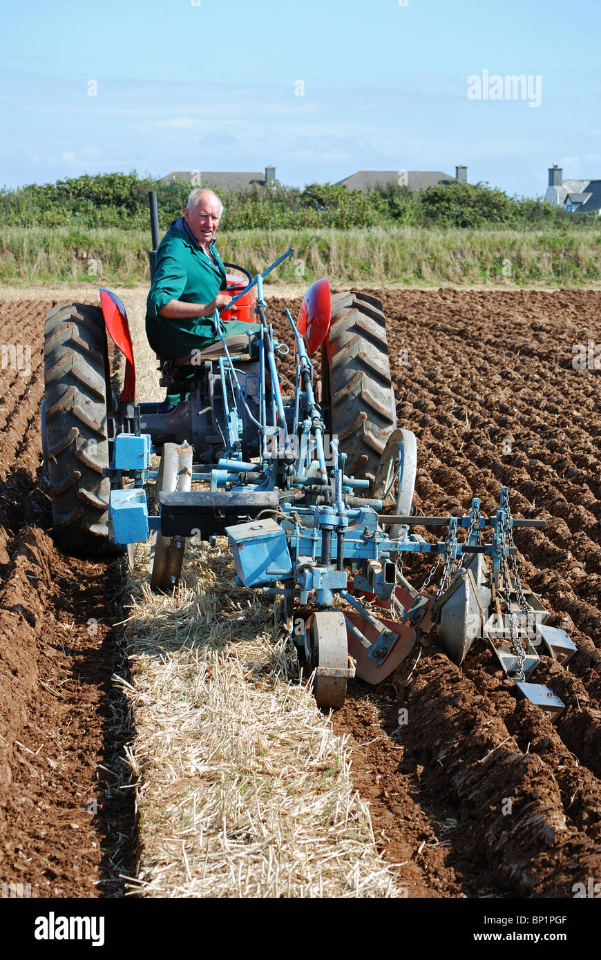 farmer using a vintage tractor to plough a field, cornwall, uk - Stock Image