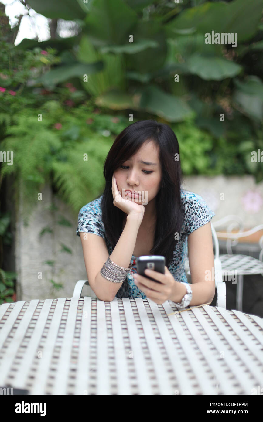 sad girl looking at her mobile phone