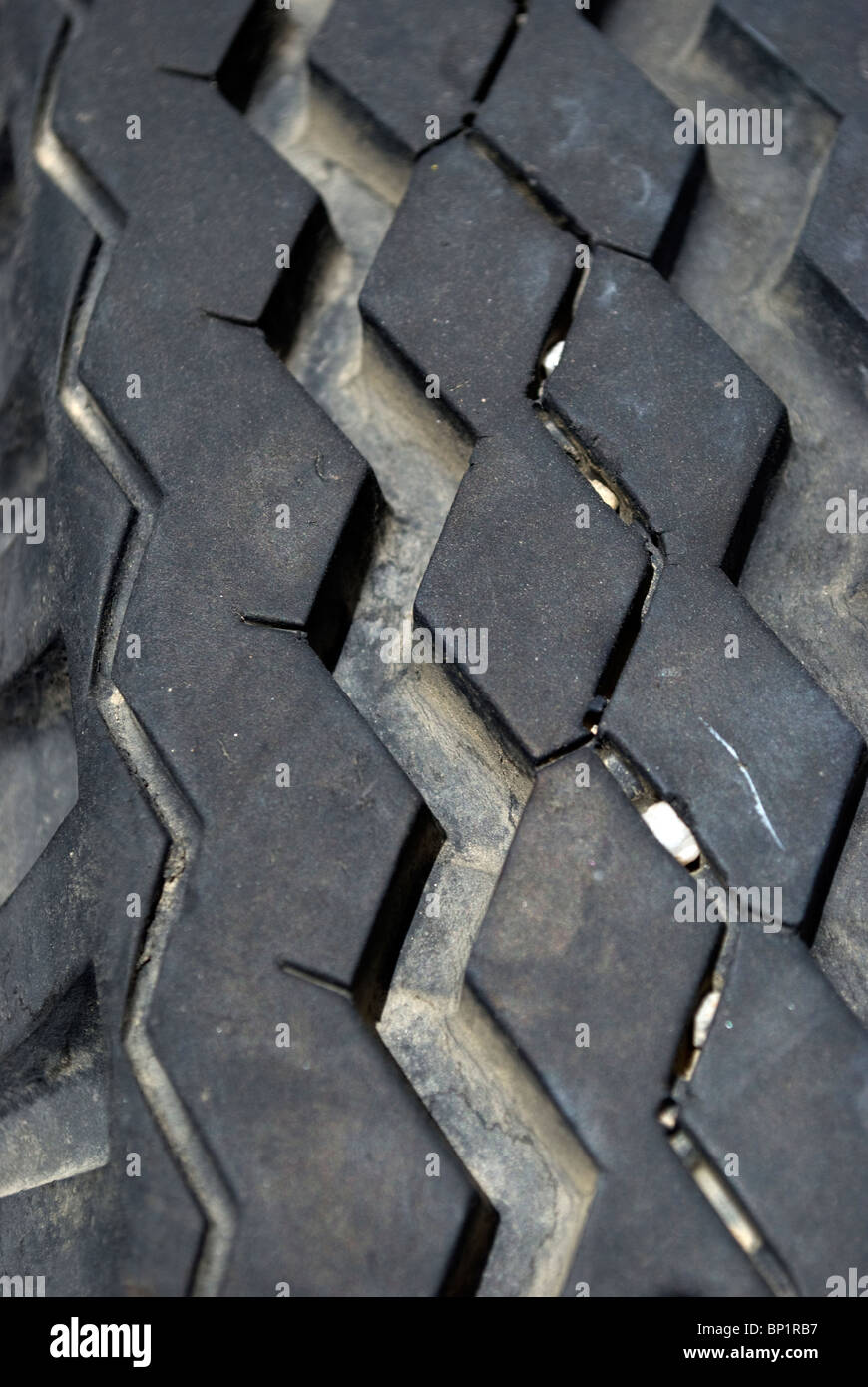 Worn and detailed tread patterns from a truck tire with lodged stones in the tire's grooves. - Stock Image