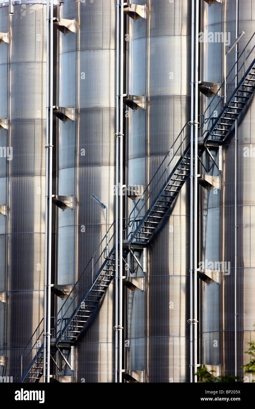 Big stainless steel tanks for chemicals in a chemical factory. Outside staircase. Stock Photo