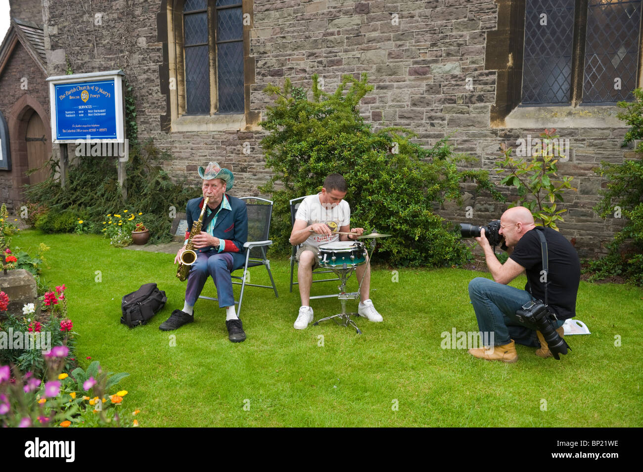 Legendary Welsh photographer Keith Morris shooting Nik Turner playing sax on church lawn during Brecon Jazz Festival - Stock Image