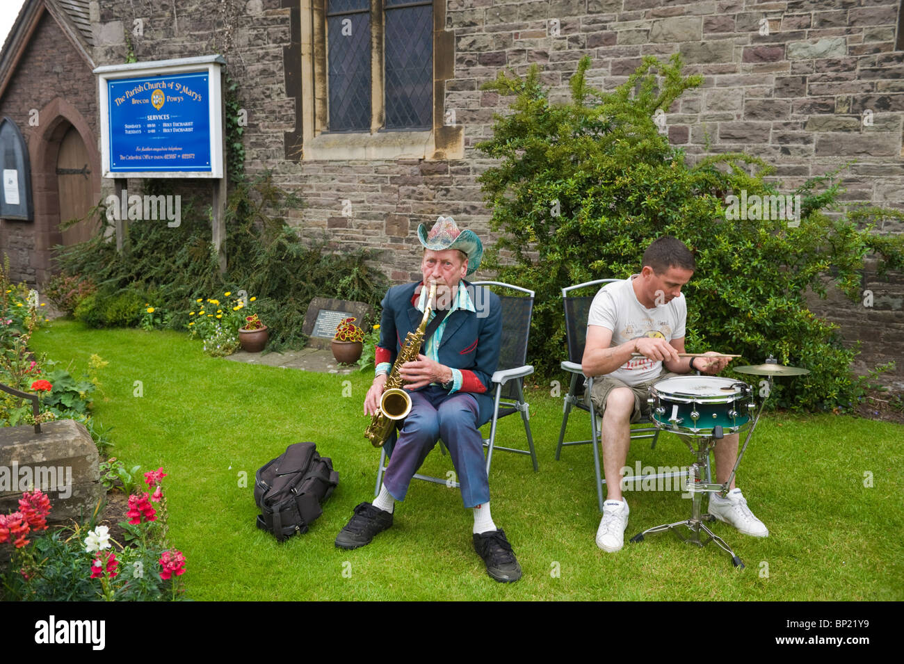 Nik Turner legendary founder member of Hawkwind busking playing sax on church lawn during Brecon Jazz Festival 2010 - Stock Image