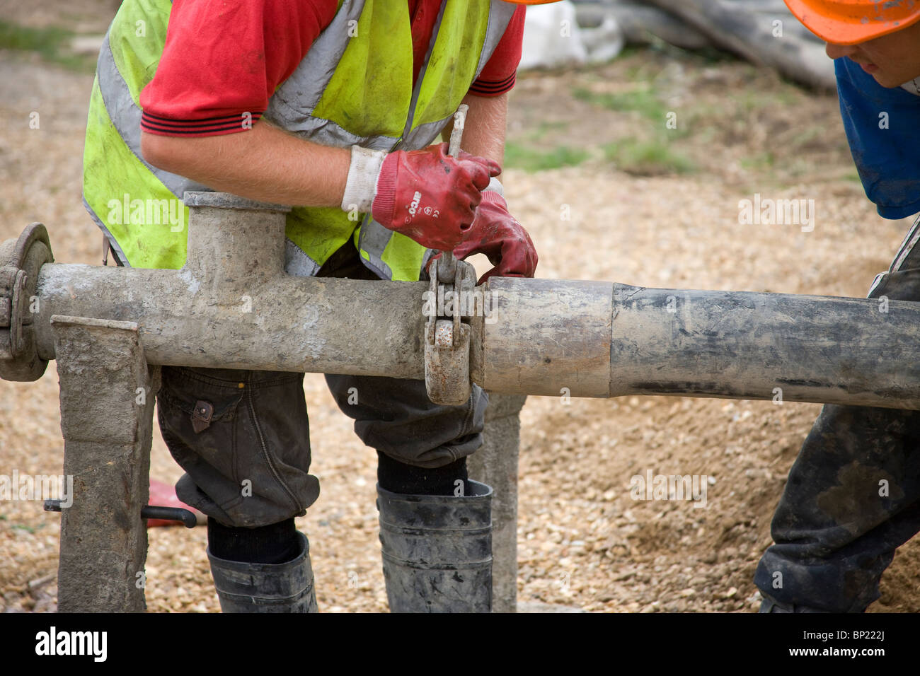 Fitting a hose connection to join lengths of hose together ready to pump concrete. - Stock Image