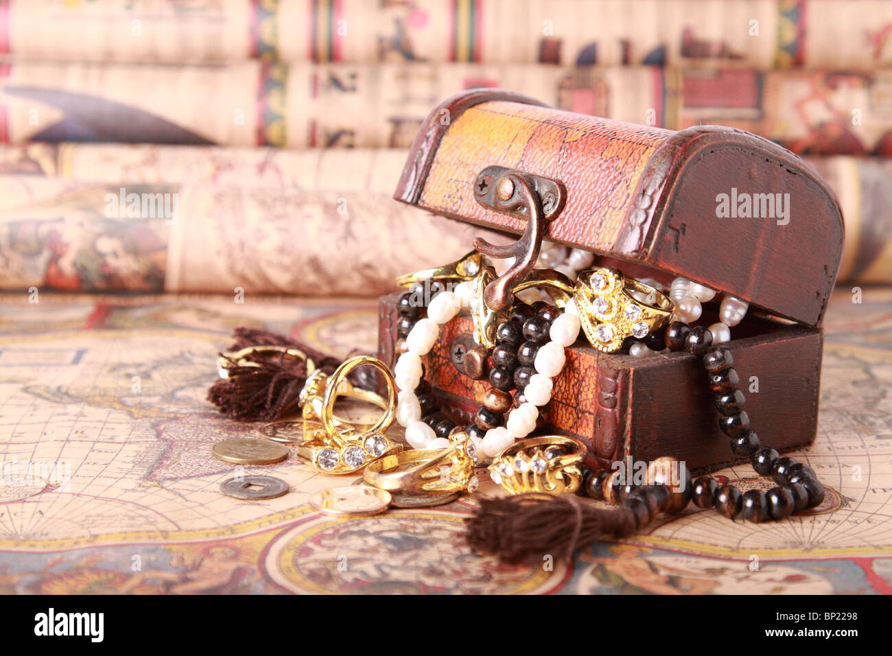 Antique chest with jewelry on vintage map - Stock Image