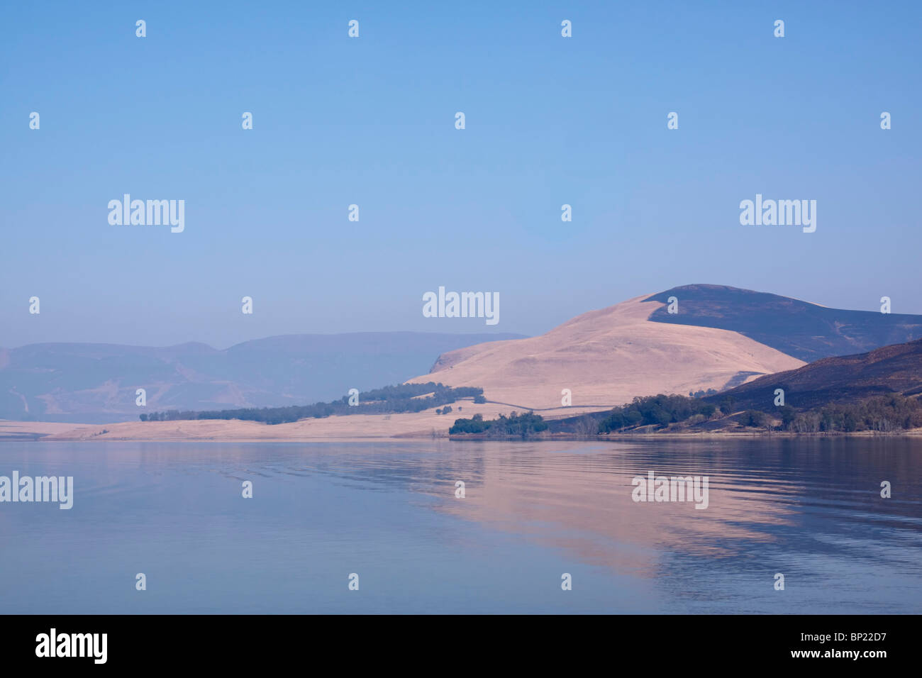 Distant hills reflected in the Midmar dam on a cloudless winter day. Midlands, KwaZulu Natal, South Africa. Stock Photo
