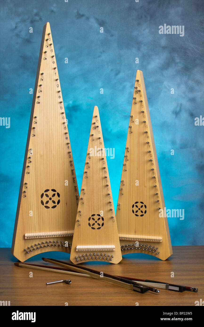 Bowed psaltery, a zither type instrument player with a short violin bow. Soprano, alto and tenor ranges are produced - Stock Image
