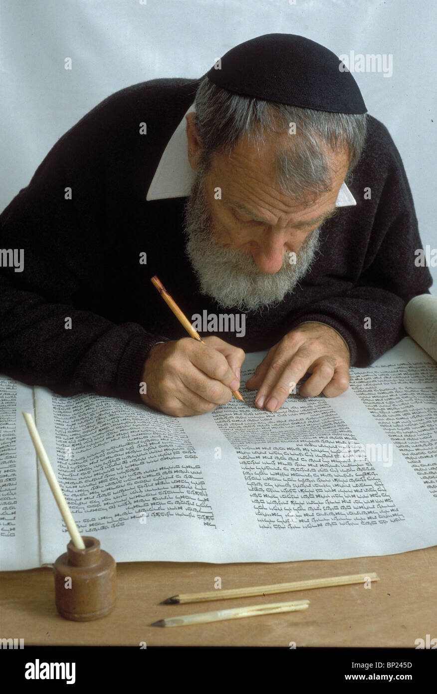 TORAH SCROLL IS BEING WRITTEN BY HAND ON PARCHMENT BY A PROFFESIONAL SCRIBE USING TRADITIONAL WRITING TOOLS REED - Stock Image