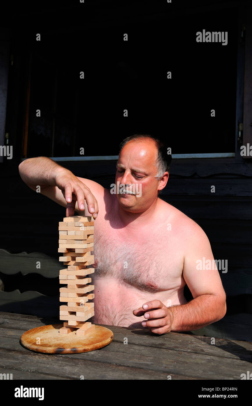 Mature Man playing a tricky board game. - Stock Image