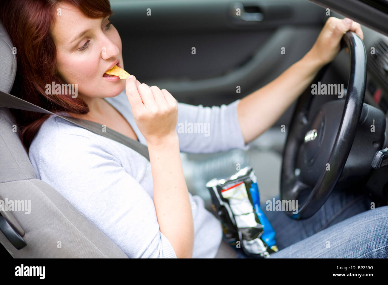 Woman snacking whilst driving - Stock Image