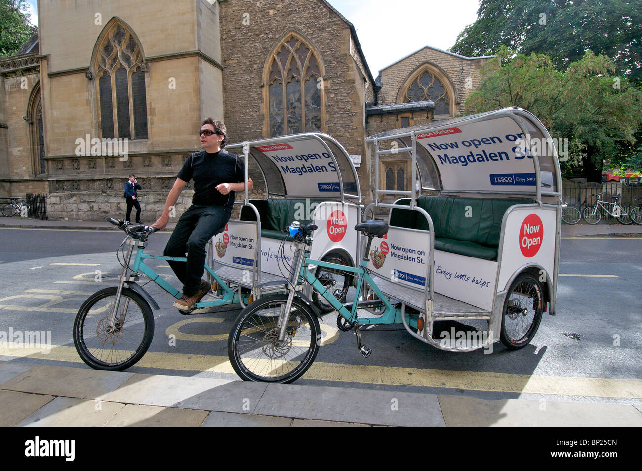 Oxford, England - Tricycle rickshaws covered in advertising slogans on the streets of the city - Stock Image