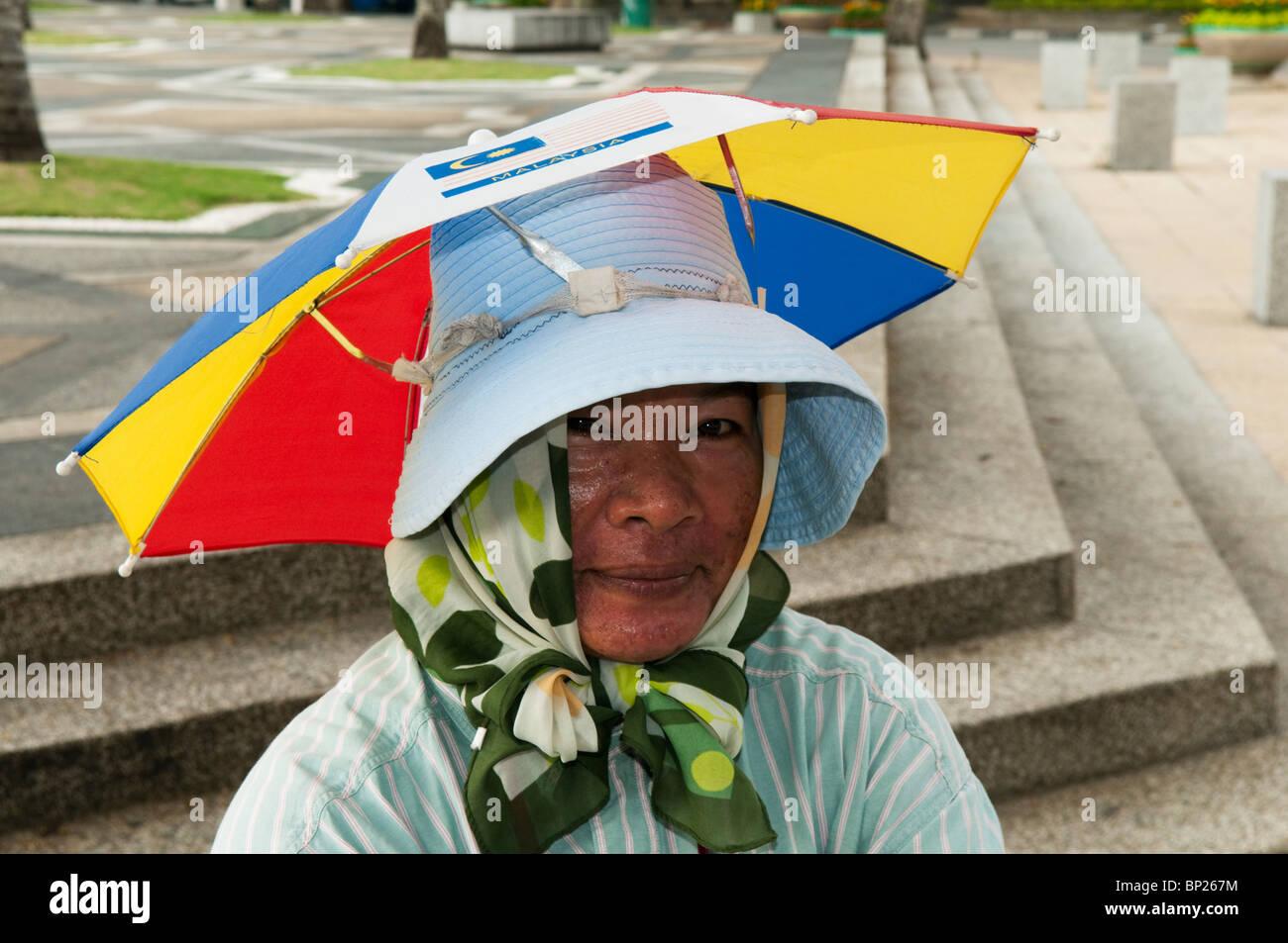 077d15c30b249 Woman with funny umbrella hat by Masjid Negara in Kuala Lumpur Stock ...