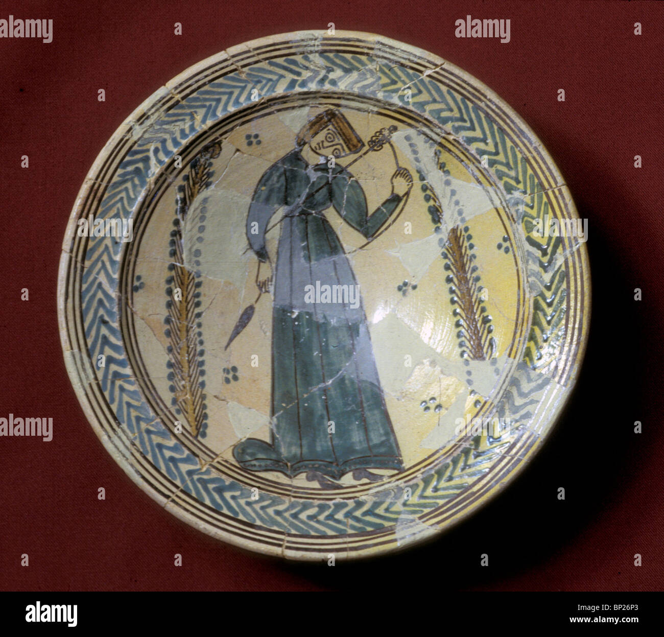 1229. CRUSADER PERIOD PAINTED CERAMIC PLATE DEPICTING A WOMAN SPINNING YARN - Stock Image