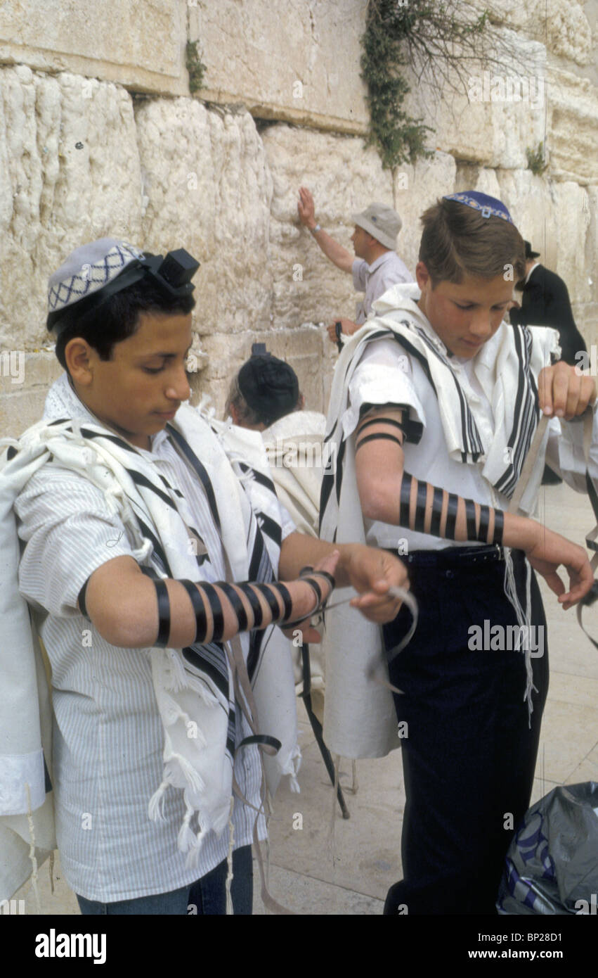 2074. BOYS PUTTING ON 'TEFILIN' (PHYLACTERY) AS PREPARATIONS FOR THEIR PRAYING AT THE WESTERN WALL - Stock Image
