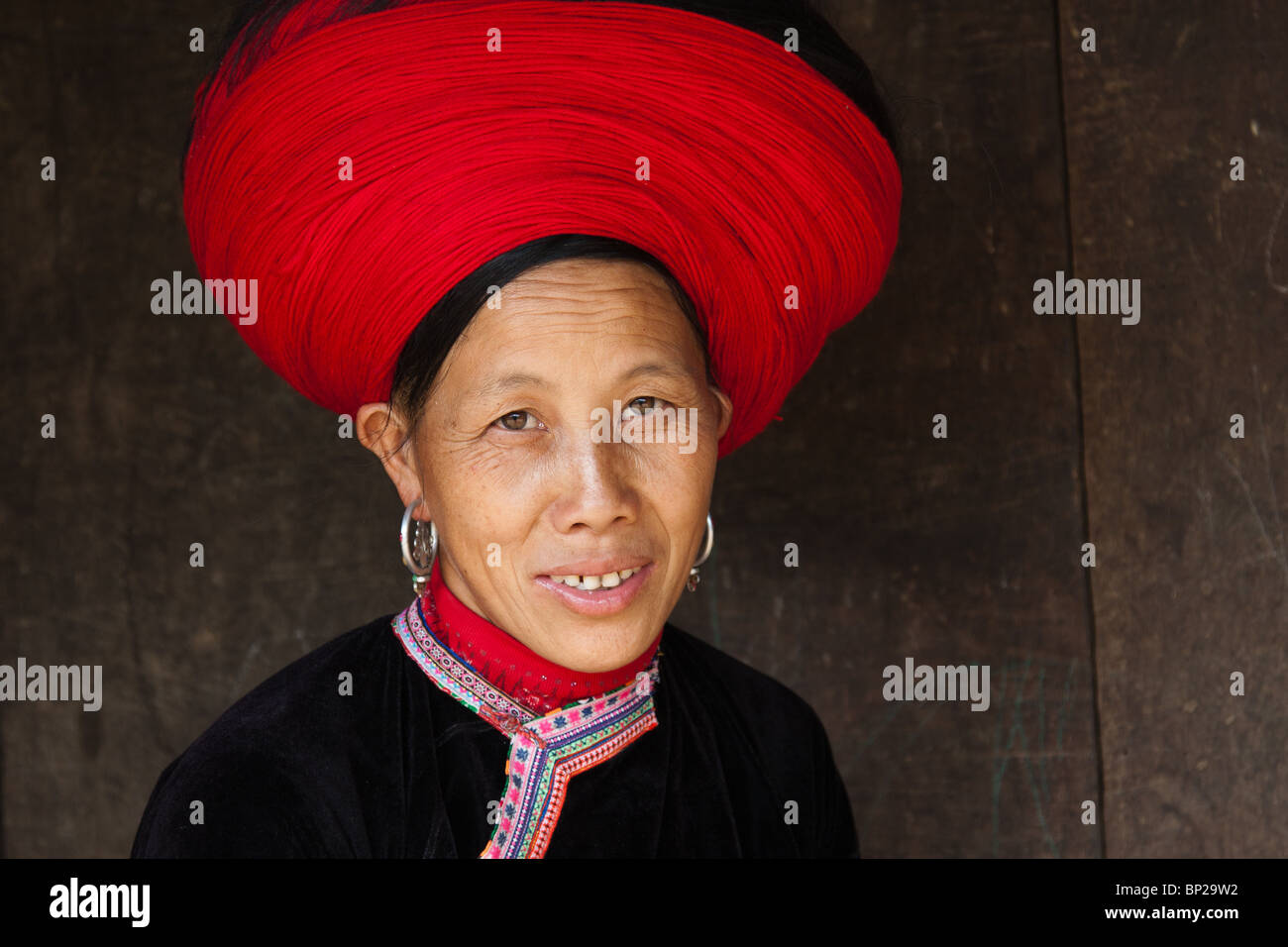 hmong woman with headress made of red yarn - Stock Image