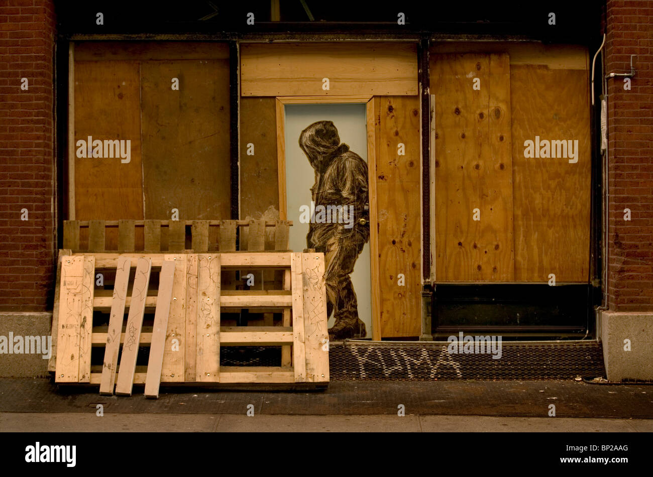 Graffiti art showing a man in a hoody painted in a wooden doorway, in the Soho district of New York City, USA. - Stock Image