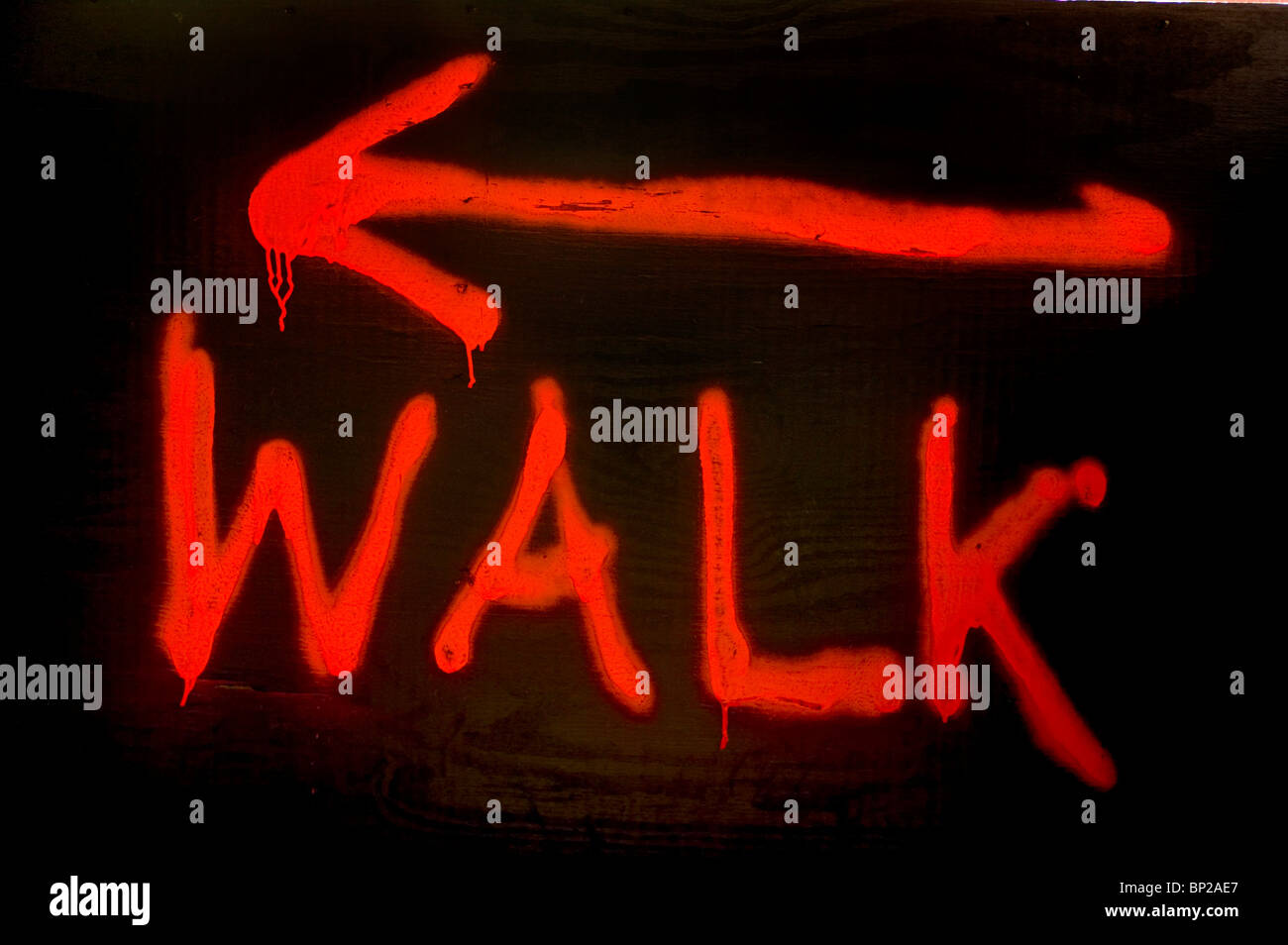 Red painted walk sign on a building site directing pedestrians on 42nd Street, Manhattan, New York City. - Stock Image