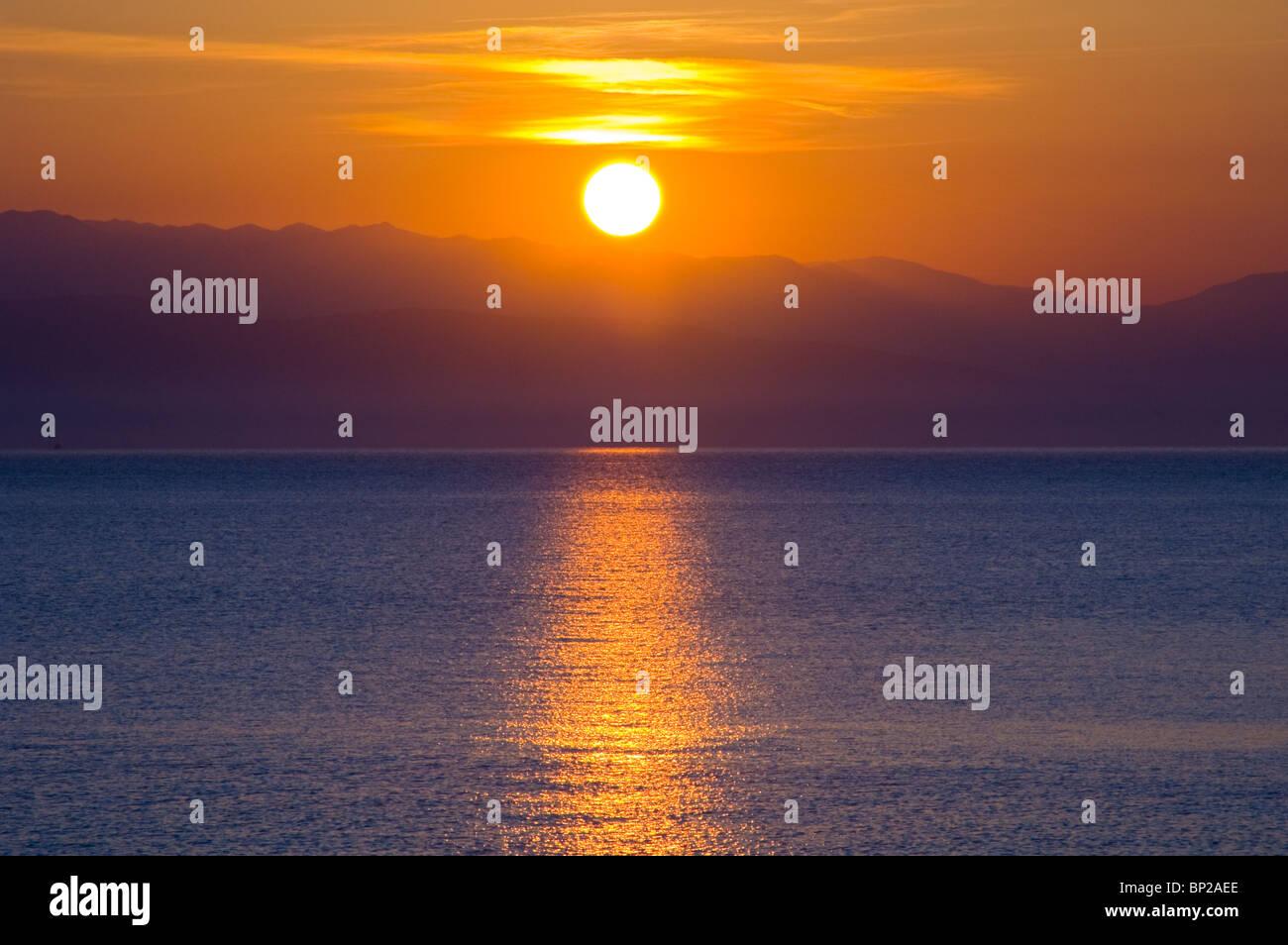 Golden sunrise over the Albanian mountains from Sidari on the Greek island of Corfu Greece GR - Stock Image