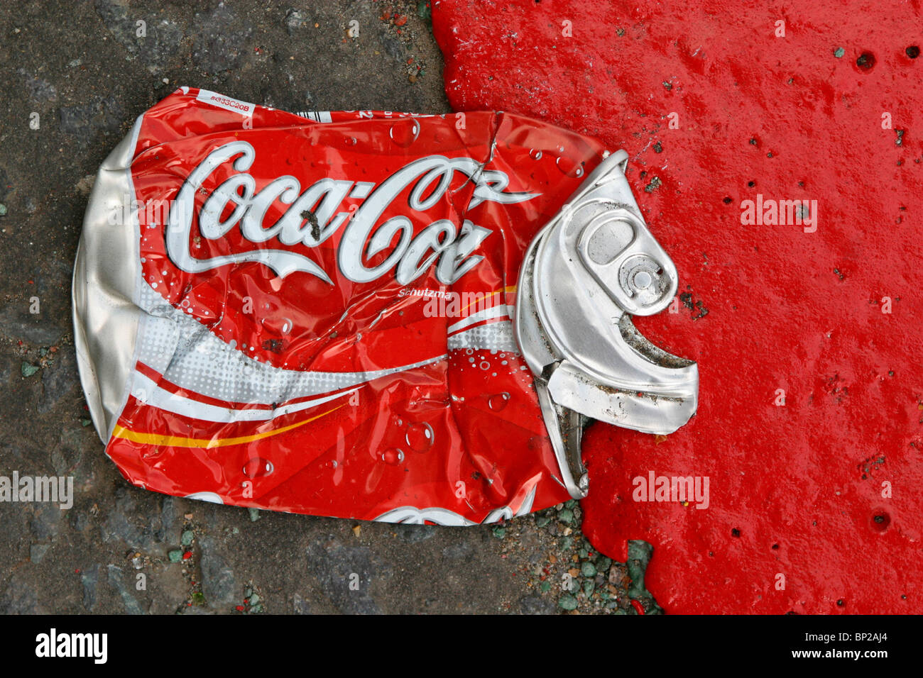 A Coca Cola can flattened in the road next to a red route road marking in bright red paint, London, UK. - Stock Image