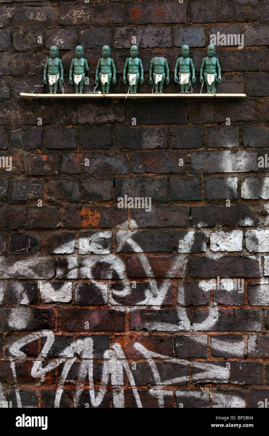 Little green figurines on a shelf 10 ft high on the inside of a railway bridge, London, Brick Lane. - Stock Image