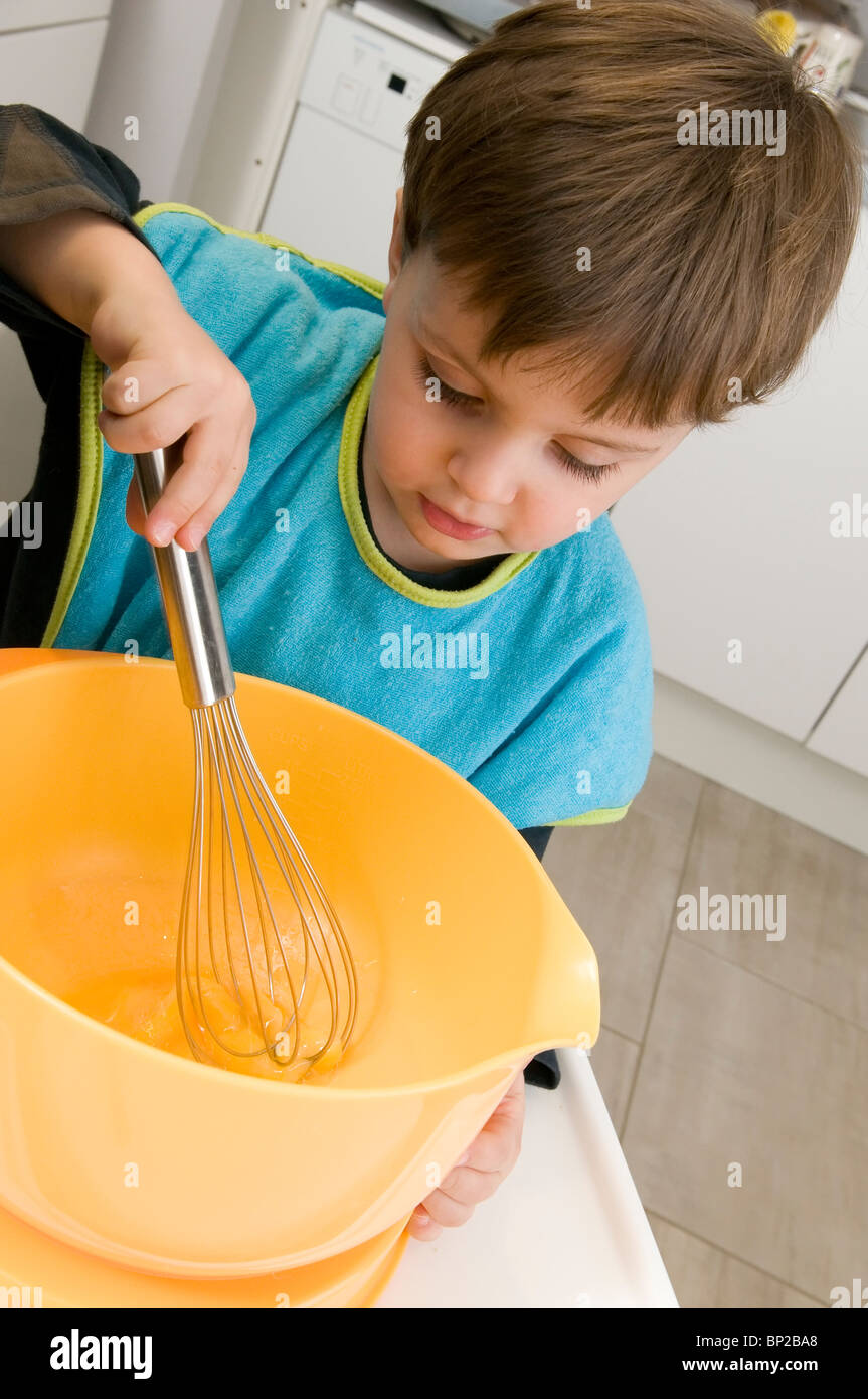 Emile - 2 and 1/2 - is preparing his omelette - Stock Image