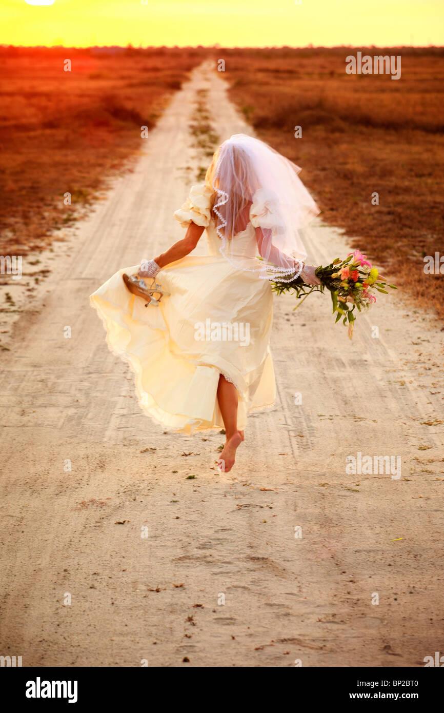 Runaway bride down dirt road - Stock Image