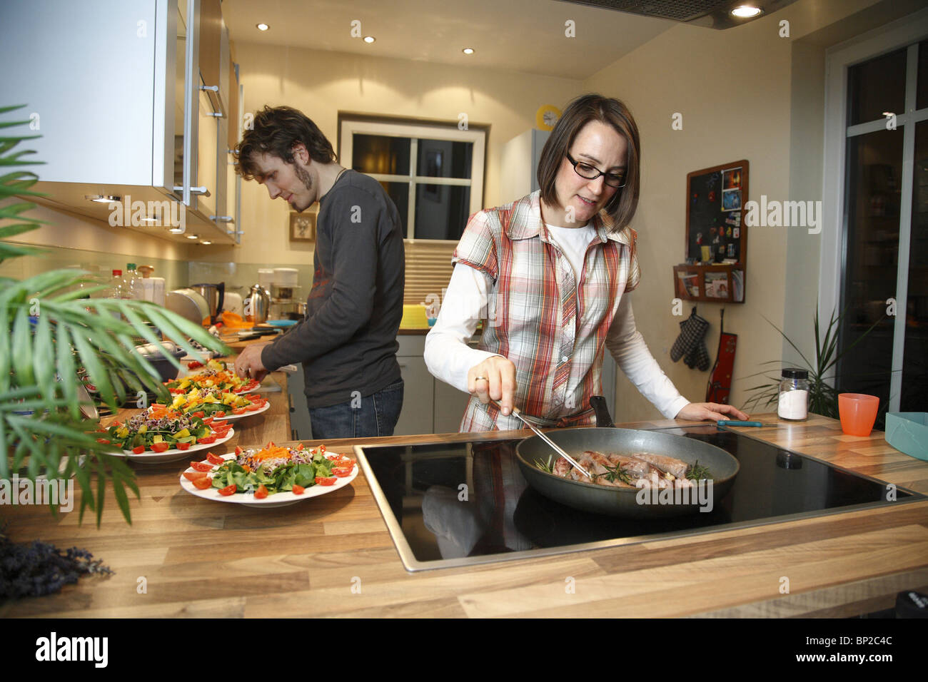 A couple cooking together - Stock Image