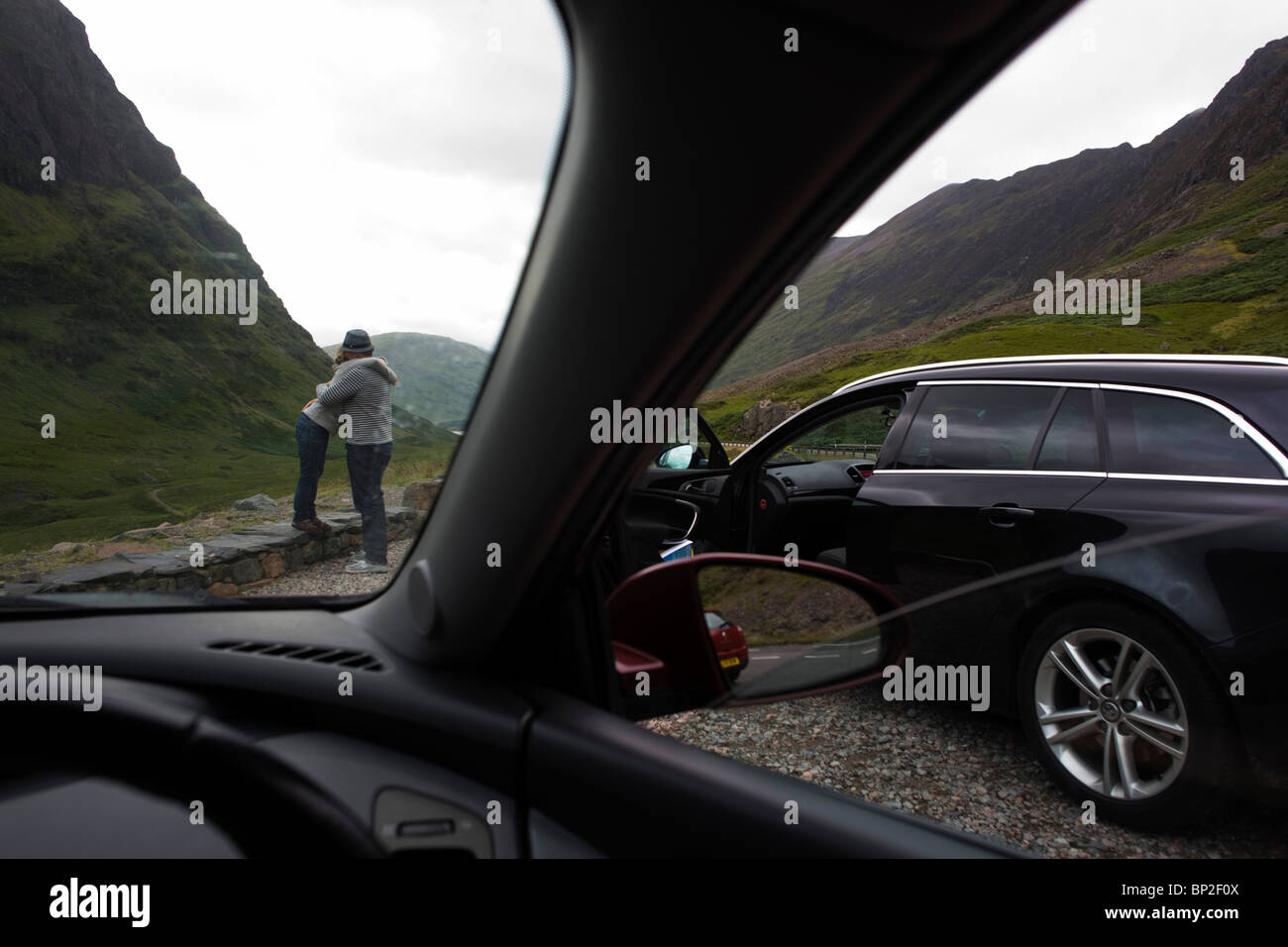Couple's spontaneous hug during stopped car journey through Glencoe, Scotland. - Stock Image