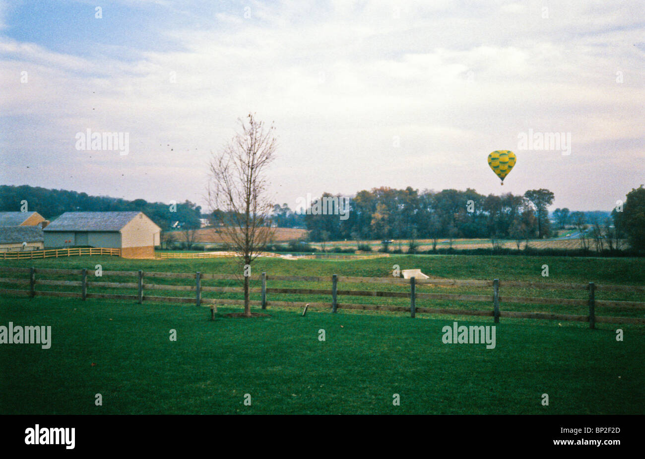 Hot air balloon riders soar , float over Lancaster farm fields, early morning. Stock Photo