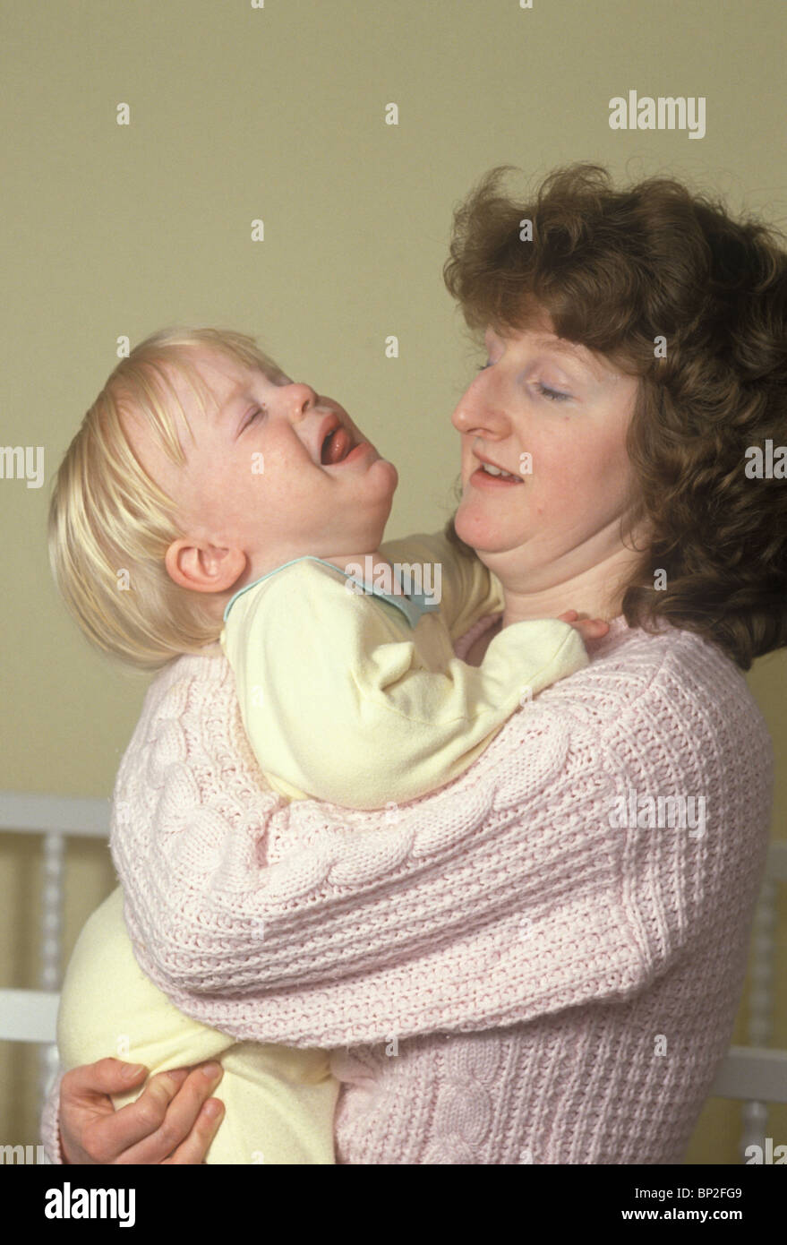 mother holding struggling toddler in throes of tantrum - Stock Image