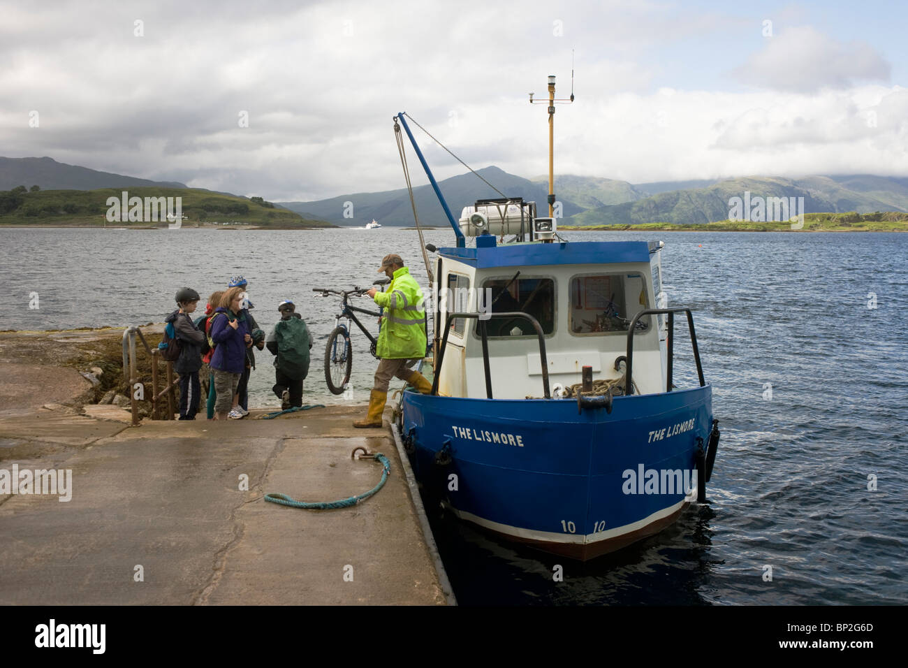 Foot passengers embark on short journey from Isle of Lismore to Port Appin, a regular ferry service for local community. - Stock Image