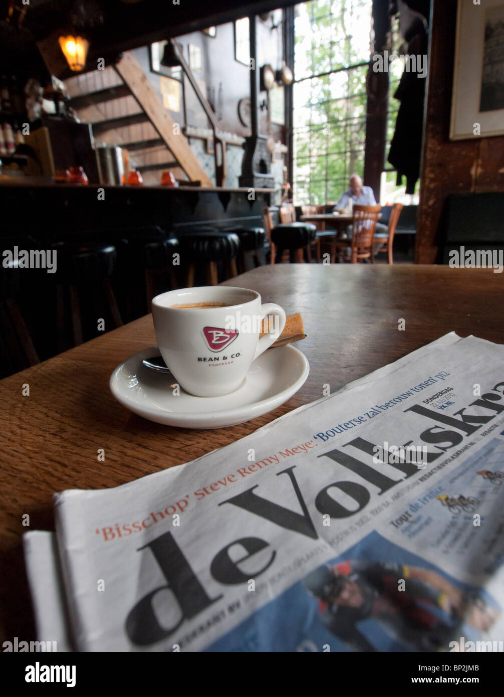 Detail of coffee and local newspaper in old Cafe Het Papeneiland in Jordaan district of Amsterdam in The Netherlands - Stock Image