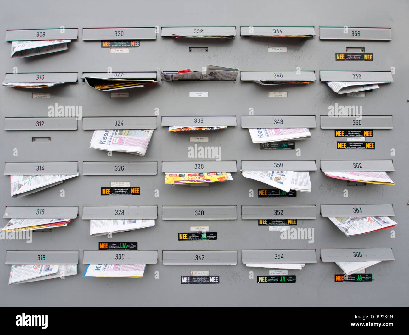 Apartment building letterboxes full of junk mail in Amsterdam The Netherlands - Stock Image