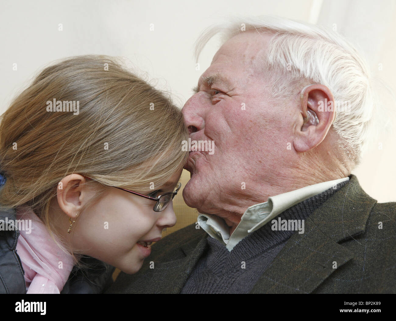 Grandfather kissing his granddaughter on the forehead - Stock Image