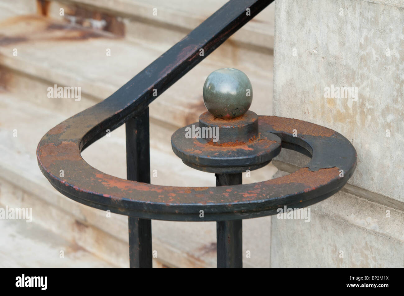 A rusty but usable wrought iron handrail provides a functional architectural detail. - Stock Image