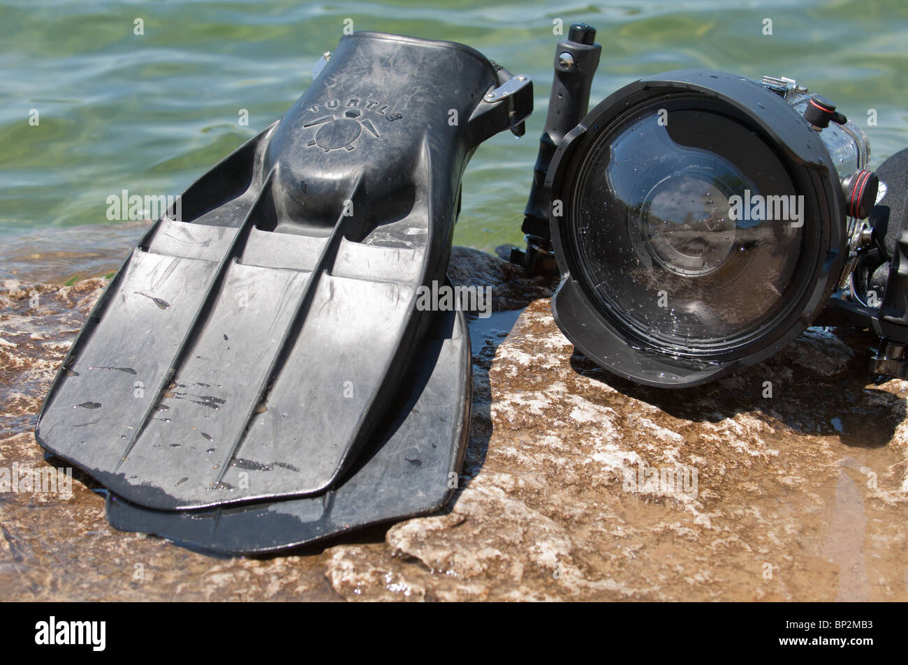 Dive fins and underwater camera housings can commonly be found amongst most scuba divers. - Stock Image