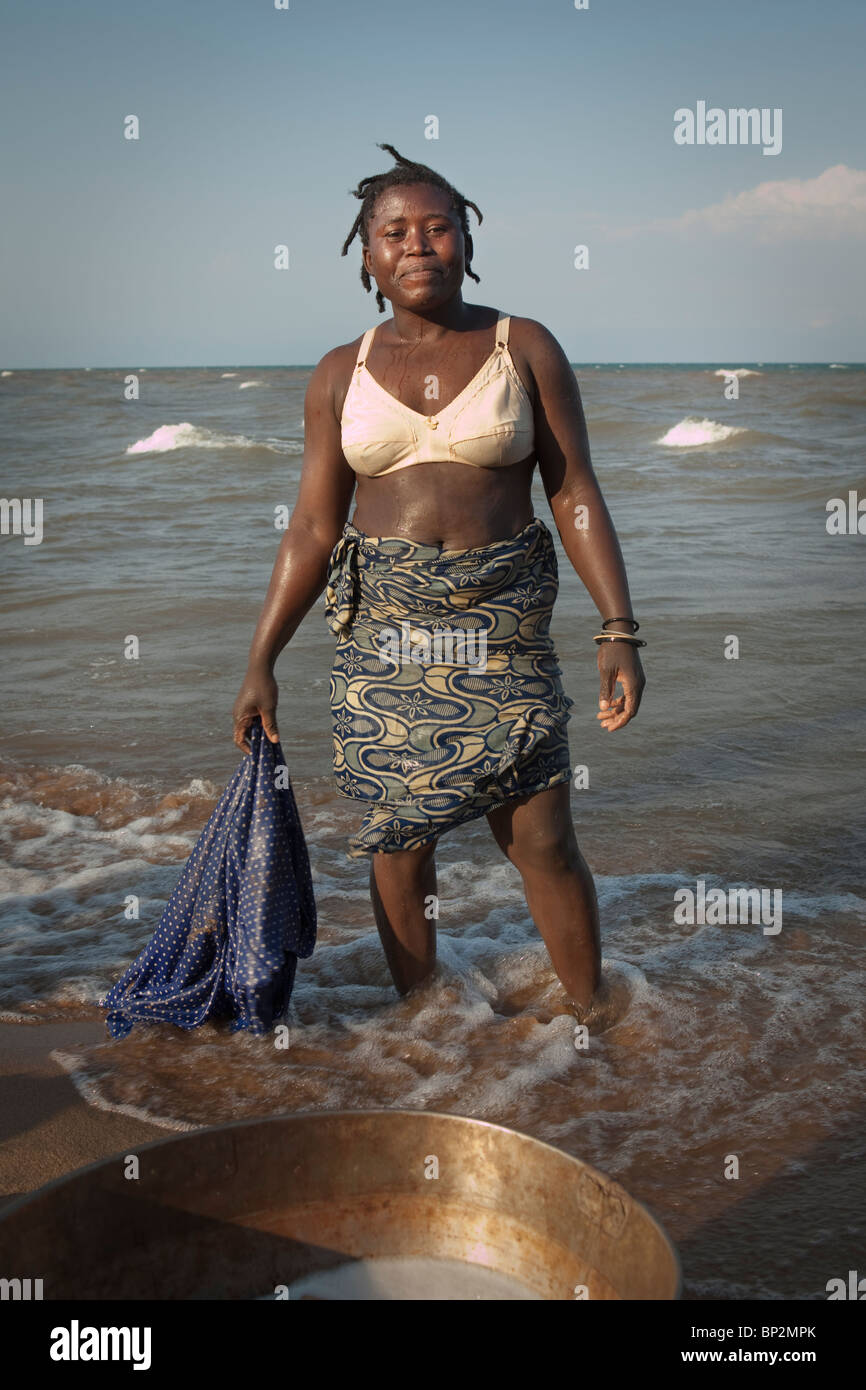 A washer woman stands along the shores of Lake Malawi, Southen Africa. Stock Photo