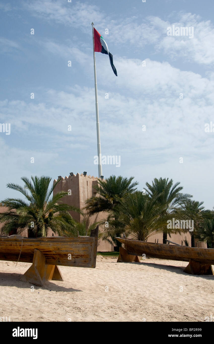 Mud-brick fortress with flag flying and traditional boats beached, at the Heritage Village, Abu Dhabi - Stock Image